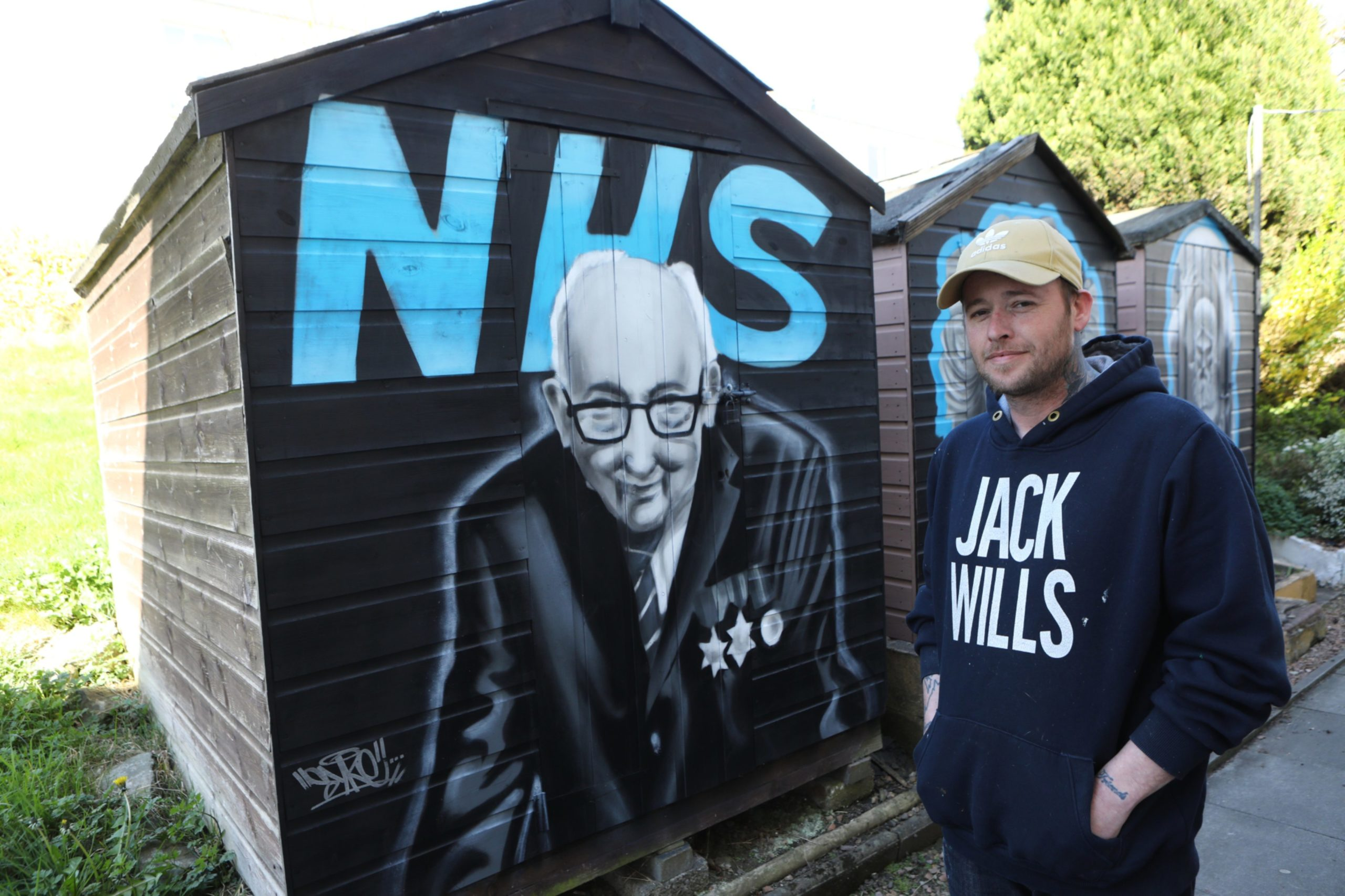 Symon beside his tribute to fundraiser Captain Tom Moore, on the sheds in Ellengowan Drive.