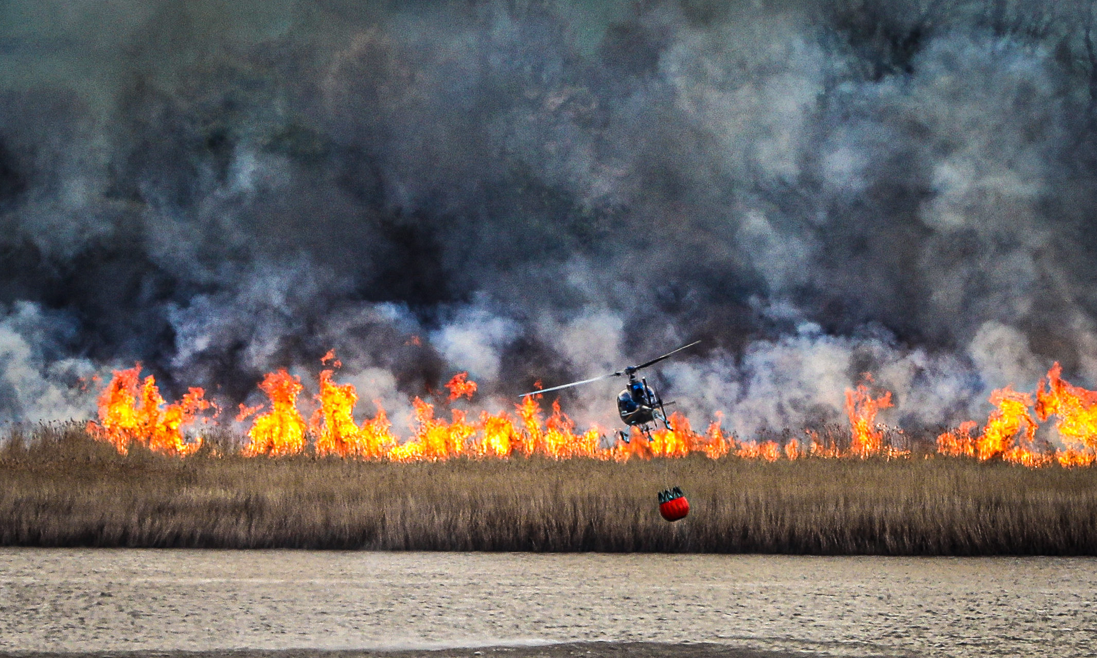 A helicopter is used to dump vast amounts of water onto the flames destroying the reed beds near Errol in Perthshire.