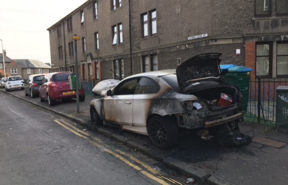A row of cars parked on the pavement, alongside one that was burned.