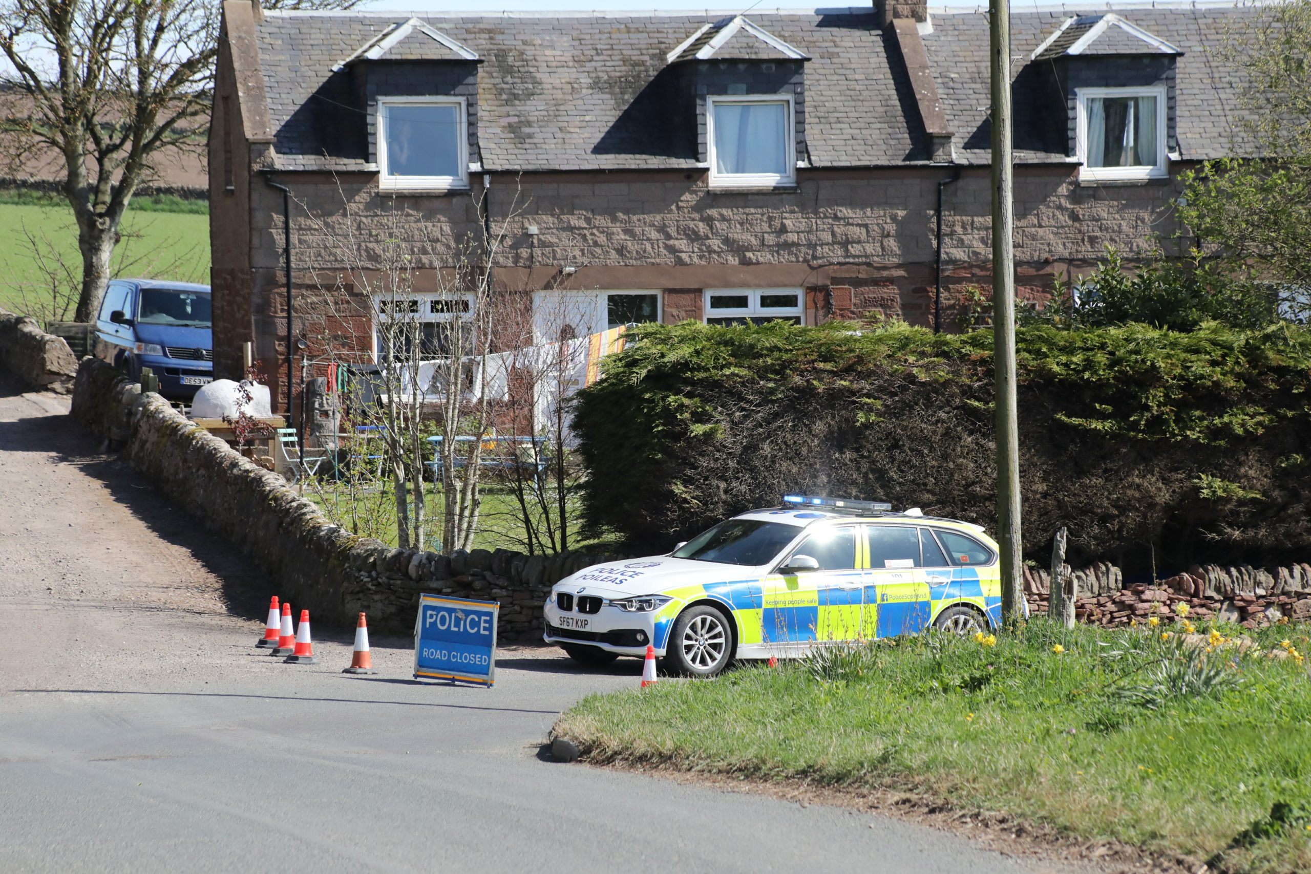 Police on the main road into Auchmithie after a cyclist died in an accident.