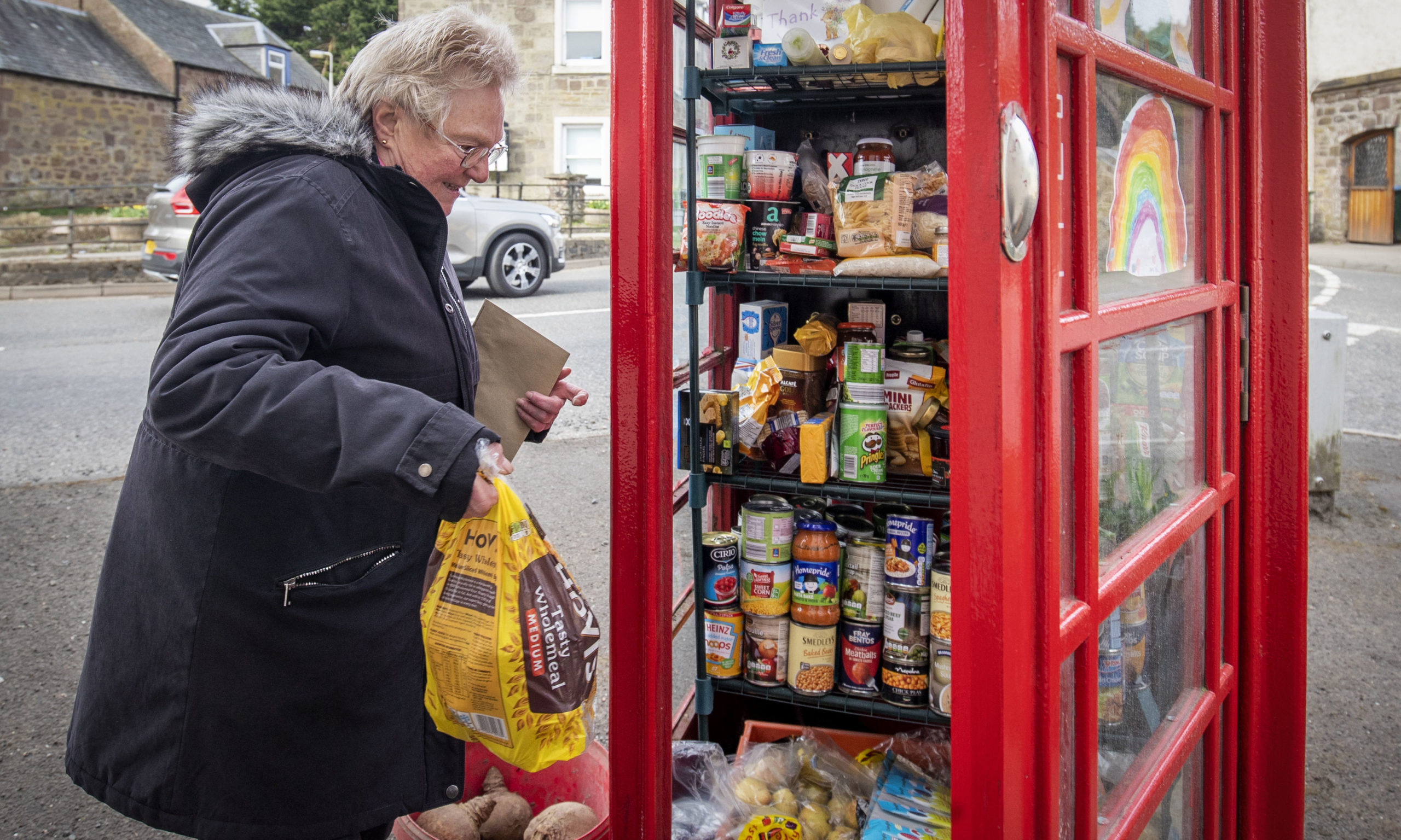 Local residents use the community food larder in Muthill, near Crieff in Perthshire, which was set up using the old village phone box as a food collection and donation point as the UK continues in lockdown to help curb the spread of the coronavirus. PA Photo. Picture date: Tuesday April 14, 2020. See PA story HEALTH Coronavirus. Photo credit should read: Jane Barlow/PA Wire