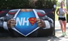 A runner passes street art in appreciation of the NHS placed near to the Francis Drake Bowls Club in Hilly Fields Park, in Lewisham.