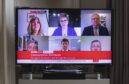 """Scotland's First Minister Nicola Sturgeon and other party leaders are seen on television in a living room during the broadcast of a """"virtual"""" session of First Minister's Questions."""