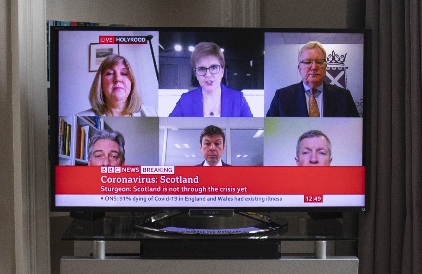 "Scotland's First Minister Nicola Sturgeon and other party leaders are seen on television in a living room during the broadcast of a ""virtual"" session of First Minister's Questions."