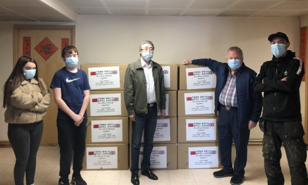From left: Kaela Mak, Damon Mak, Consul General Ma Qiang, David Valentine and Damian Mak who volunteered to take the masks to Angus from Edinburgh.