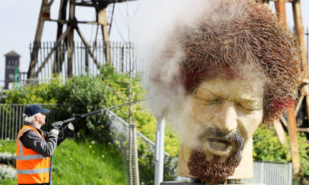 Ross Sheridan of P.Mac Cleaning and Restoration services working on behalf of Dublin City Council cleans a statue of the late musician Luke Kelly in the Sherriff street area of Dublin, after it was defaced for the fourth time in the past year.