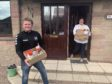 """Peter Davidson collecting a """"contactless"""" food package from Brenda Petrie."""