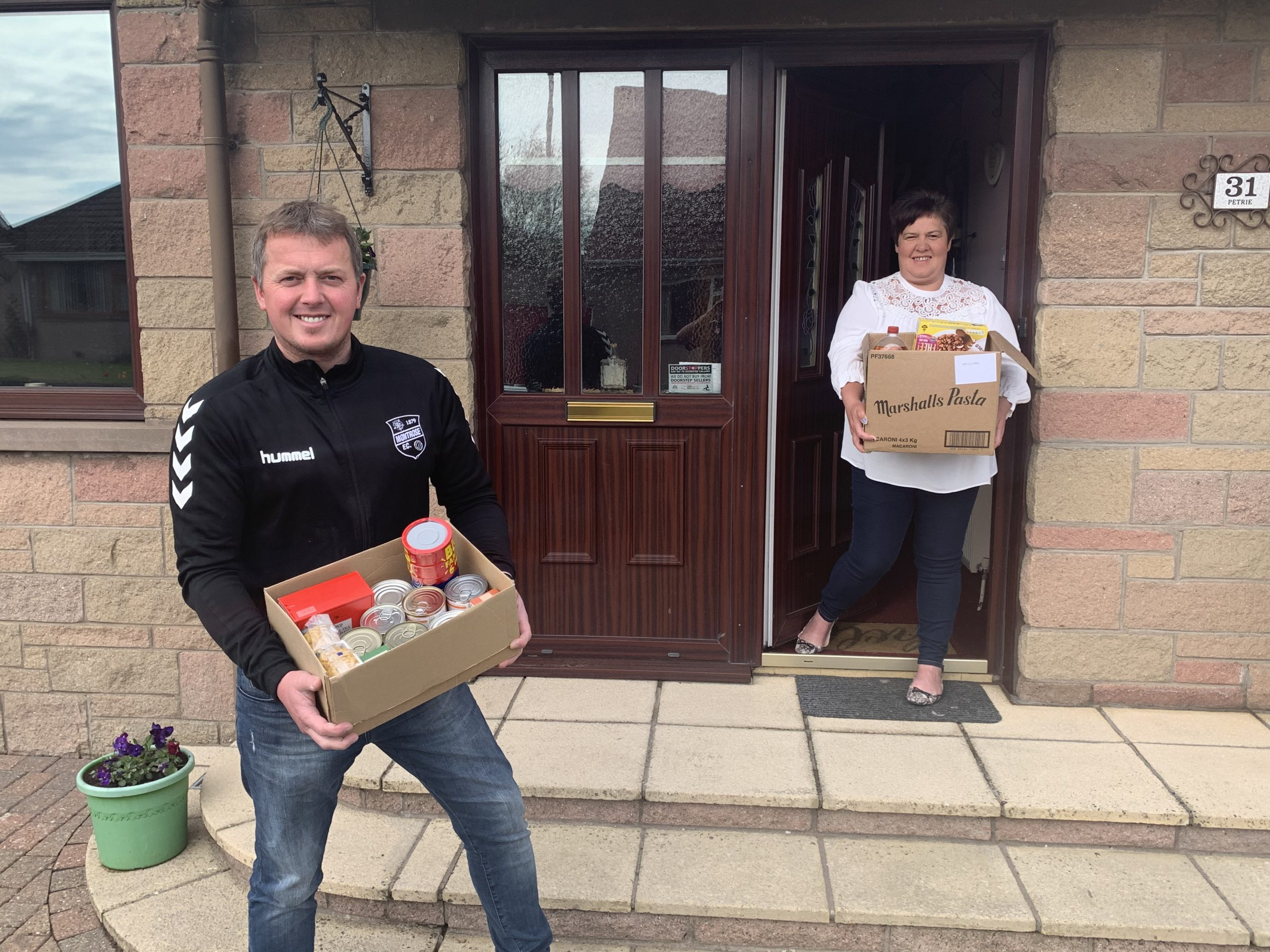 "Peter Davidson collecting a ""contactless"" food package from Brenda Petrie."