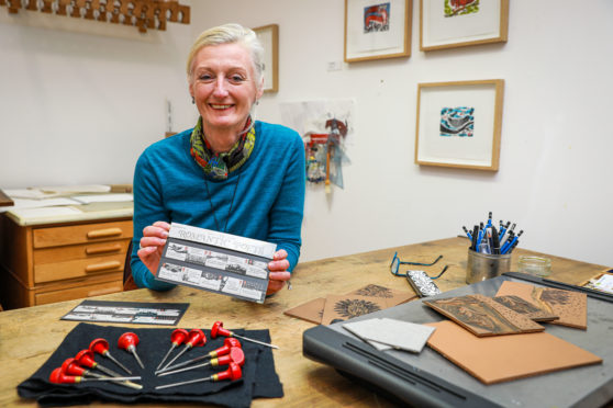 Linda Farquharson in the studio with the stamps that she helped produce.