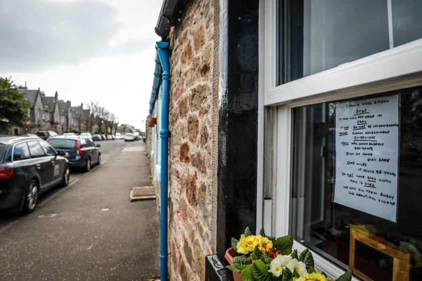 A poster in the window of a property in Crail directed to second home owners