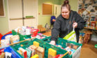 Volunteer Kirsty Hayston packs boxes of goods for clients.