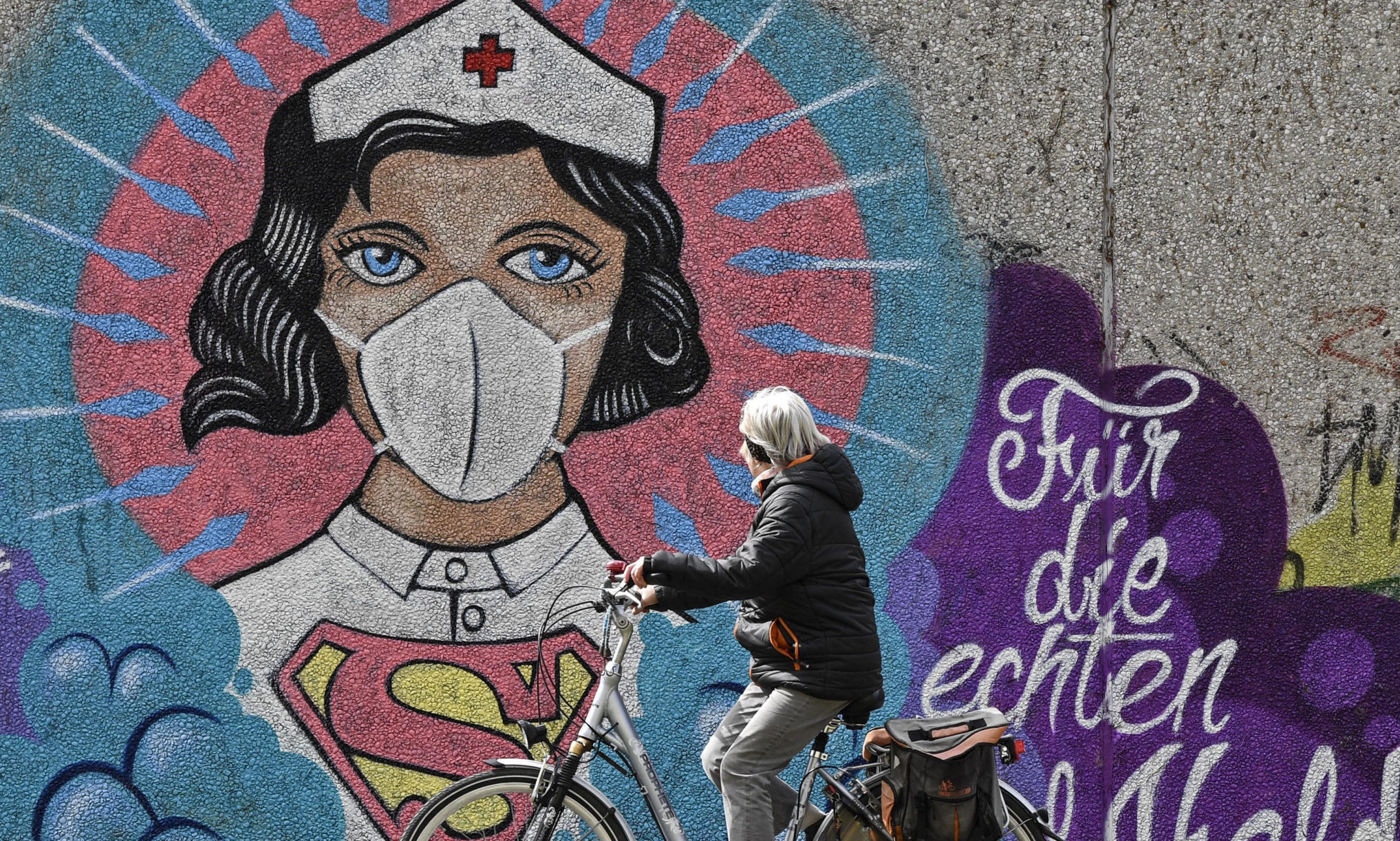 """A woman on a bicycle passes a coronavirus graffiti by street artist 'Uzey' showing a nurse as Superwoman, the lettering reads """"for the real heroes"""" on a wall in Hamm, Germany,"""