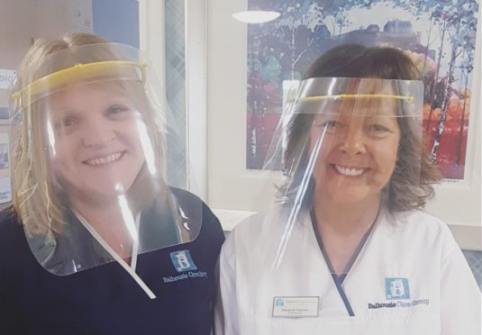Staff at Balhousie Clement Park model the visors made by Design & Technology school teachers in Dundee