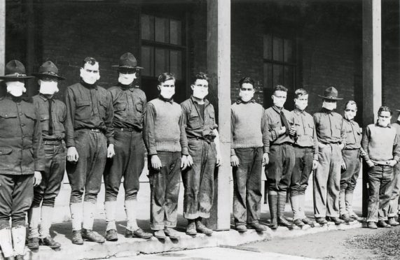 Medical personnel wear masks to protect themselves from Spanish Flu.