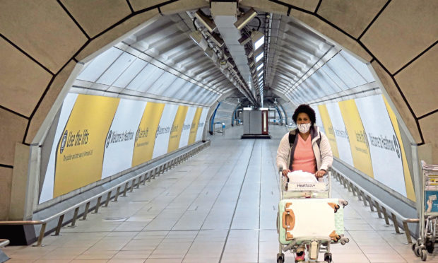 A passenger wearing a face mask is seen at Heathrow Airport in London.