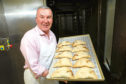 MIchael Saddler with a tray of bridies just out of the oven.