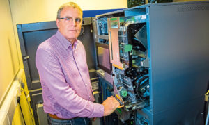 Renovite Technologies managing director Jim Tomaney examines an ATM.