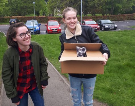 Erin (left) and Katy carry the duck in a box © John Fettes
