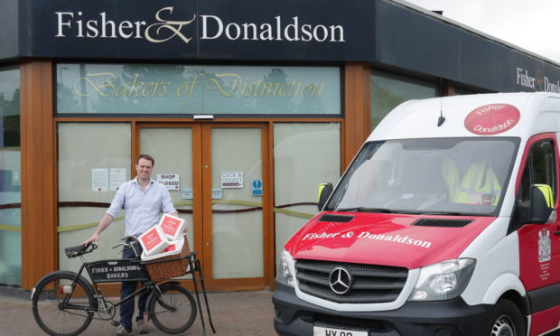 Ben Milne with his grandfather's bike at Fisher & Donaldson bakers in Cupar