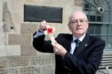 Ron Scrimgeour places a memorial cross to New Zealand namesake Sergeant Ralph Scrimgeour each Armistice Day.