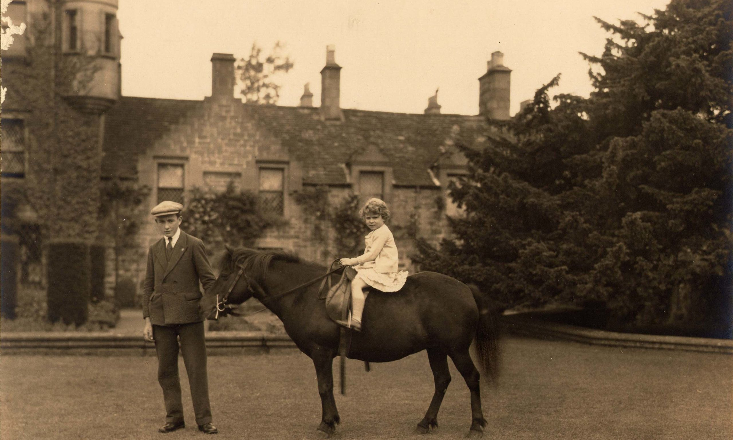 A young Princess Elizabeth, later to become Queen, on her black mare, Betty with her groom, Mr Smith, at Glamis Castle.