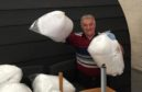 Celtic and Manchester United legend Lou Macari with the duvets sent by Fife firm Dusel Ltd.