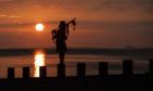 Piper Louise Marshall plays at dawn along Edinburgh's Portobello Beach