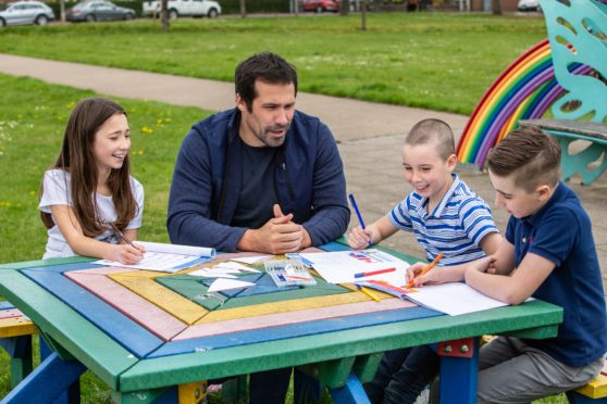 Montrose dad Mark Bradley using the activity packs with his children, Layla, Angus  and Oliver.