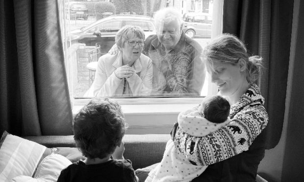 Baby Jørgen with his mother Caroline and brother Terje as they meet grandparents Ann and Alan.