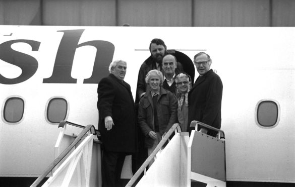Miss Jean Waddell steps from the plane at Heathrow Airport after the release from captivity in Iran of the three Anglicans. Behind her is Mrs Audrey Coleman, with Dr John Coleman, her husband, Dr Runcie, the Archbishop of Canterbury and Terry Waite.