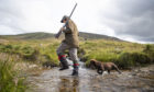 Archie Ward, with Milo the dog, member of a shooting party on the moors at the Rottal Estate in Glen Clova, near Kirriemuir, Angus, on the Glorious Twelfth, the start of the grouse shooting season.    Monday August 12, 2019. Jane Barlow/PA Wire