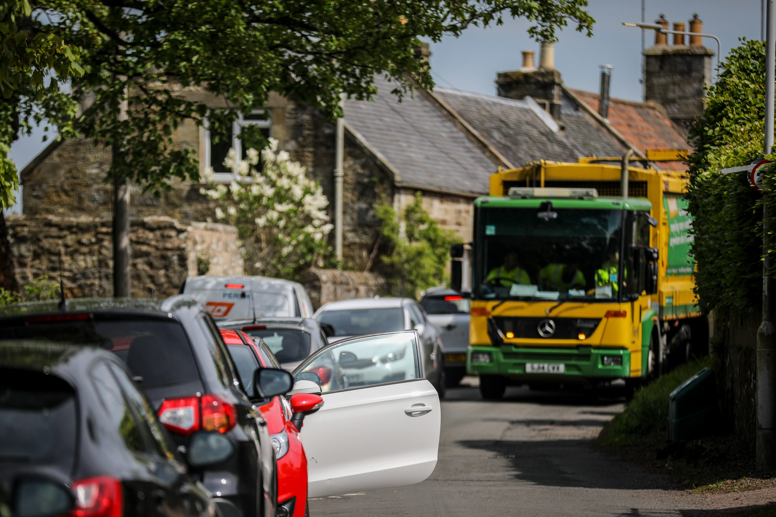 Fife Council recycling truck struggles to pass parked vehicles lining the road leading to the entrance of Falkland Estate