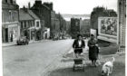 Two women and a dog walking up the Hilltown in Dundee on June 29 1961.