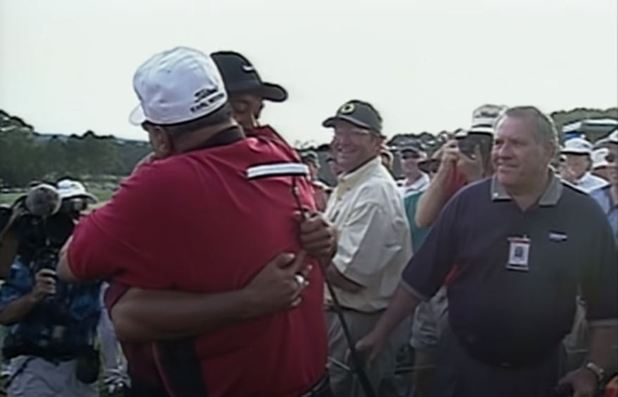 He hugs father Earl Woods, who passed away five years later