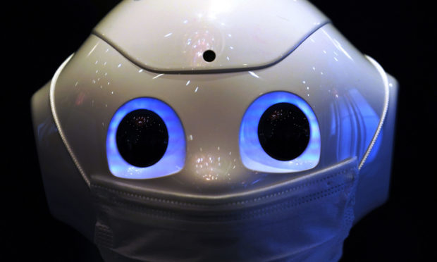 A humanoid robot Pepper wearing a face mask is placed at the door at the lobby of a hotel for the new coronavirus COVID-19 patients with mild symptoms during a media preview in Tokyo Friday, May 1, 2020. Prime Minister Shinzo Abe said Thursday he planned to extend a state of emergency beyond the scheduled end of May 6 because infections are spreading and hospitals are overburdened. (AP Photo/Eugene Hoshiko)