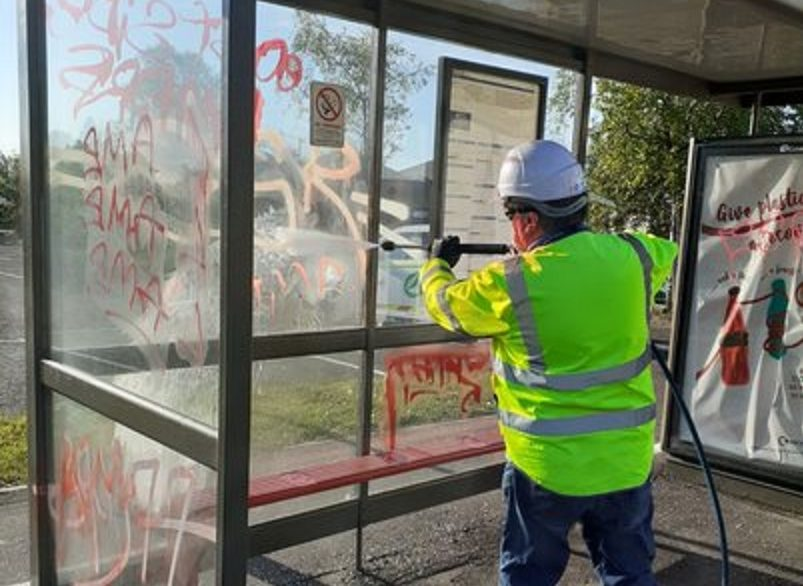 A council workman hard at work removing the graffiti from a bus shelter.