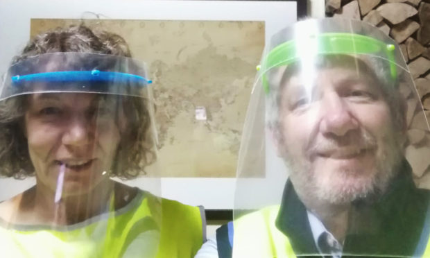 Esther and James Wilson wearing the visors while volunteering.