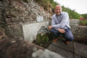 Councillor Wann next to the remains of St Ninian's well.  Mhairi Edwards/DCT Media