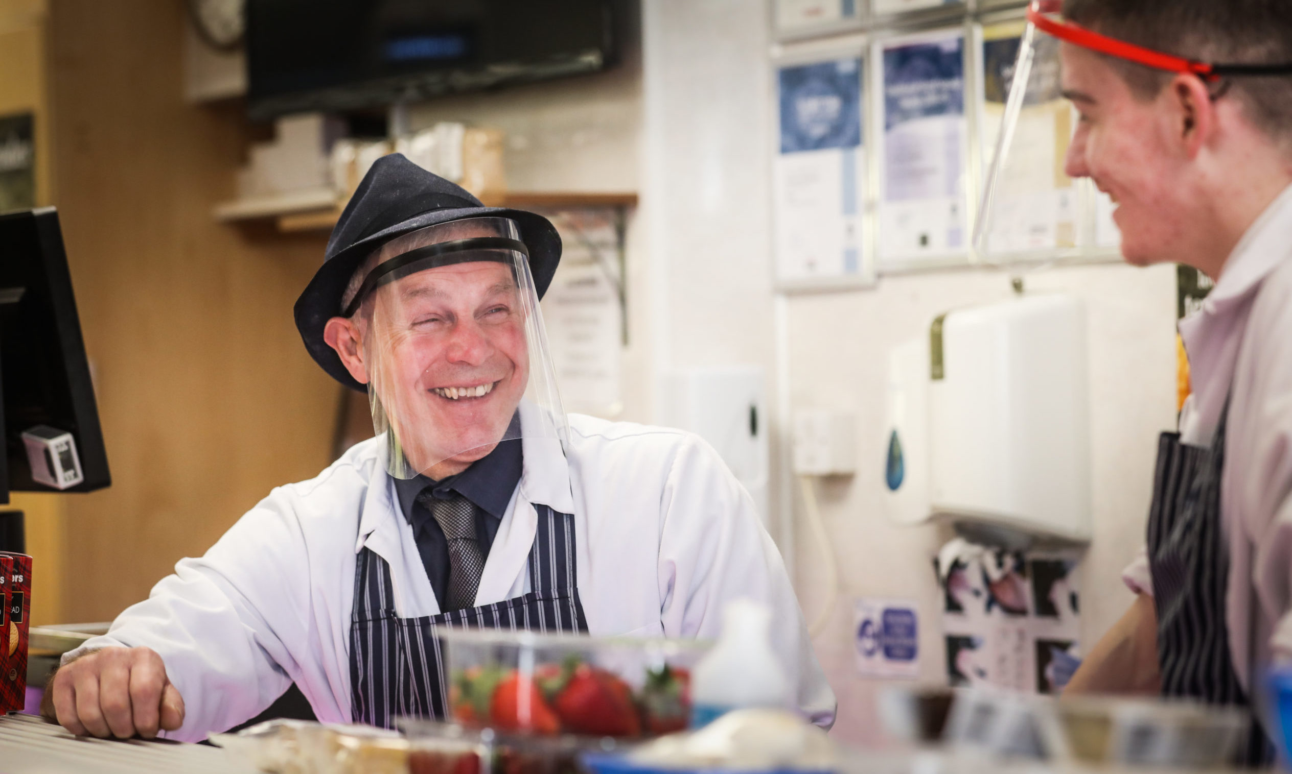 David McNee, a butcher from Hunters wears a facemask while he serves customers.