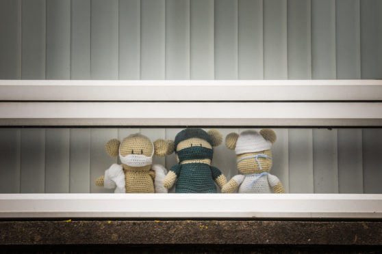 Cuddly toys are seen with masks on.
