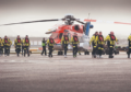 Offshore workers with a CHC Scotia helicopter at Aberdeen heliport.