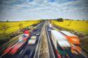 HGV Traffic on British Motorway Among Yellow Rapeseed Fields; Shutterstock ID 638800744; Purchase Order: -