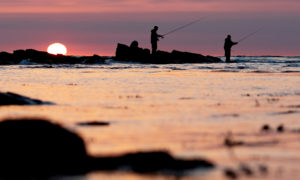 Mandatory Credit: Photo by James Marsh/Shutterstock (10661644d) Two fishermen are seen at Peveril Point, Swanage as the sun rises. Seasonal Weather, Peveril Point, Swanage, UK - 28 May 2020