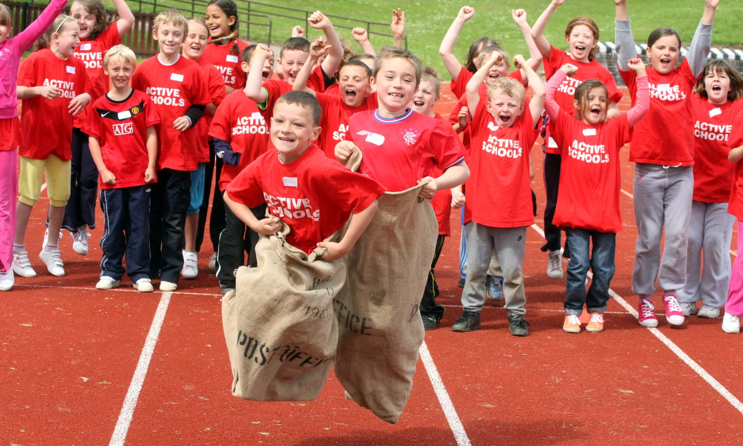 Primary School mini Highland games at Caird Park, Dundee - Baldragon feeder schools of Downfield, Sidlawview and Ardler PS  with Michael Gillan of Ardler Primary School and Mark Bertinshaw of Downfield during a sack race