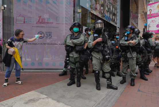 Riot police standing guard as a woman tries to cross the street in the Central district of Hong Kong.