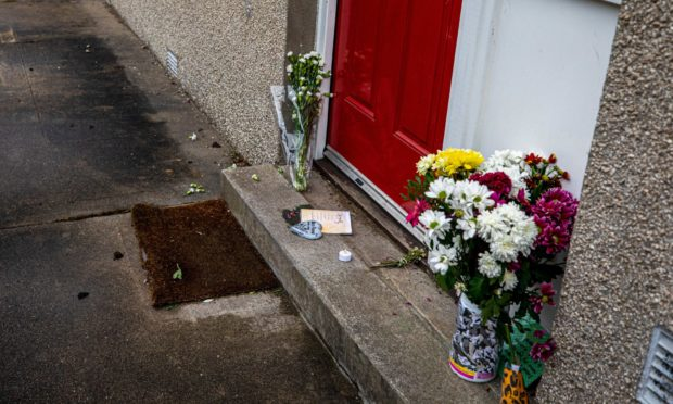 Floral tributes left at the house in Almondbank