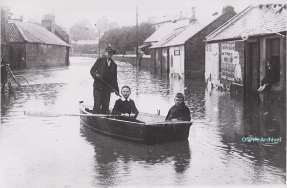 Young boys in a boat after Cupar floods in 1916.