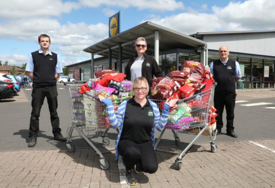 Left to right: Gordon Thompson, store Deputy Manager; Debbie Hay of CATH; Pam Lindsay of CATH (kneeling); and Ken McNamee, Shift Manager. Picture: Gareth Jennings.