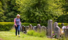 Gillian Brock at Comrie Cemetery where gravestones are obscured by weeds