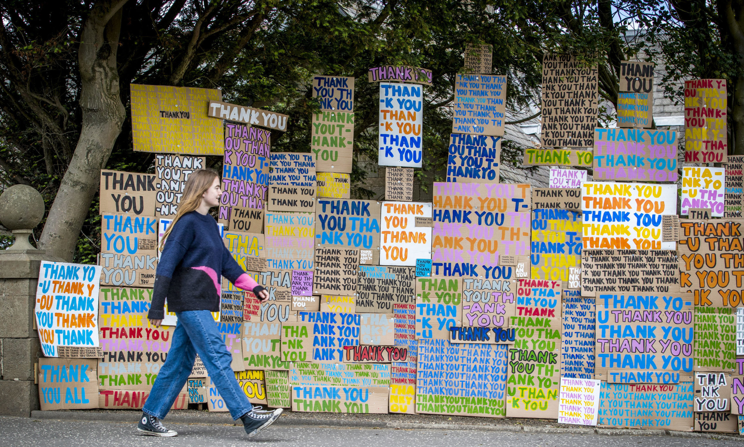 """Hermione Wilson walks past a new artwork at Jupiter Artland, Edinburgh, created as a tribute to the NHS titled """"A Thousand Thank Yous"""" originally devised by the late Allan Kaprow which consists of colourful painted messages on cardboard and has been directed remotely by London-based artist Peter Liversidge. PA Photo. Picture date: Monday June 8, 2020. The Jupiter Artland sculpture park recently re-opened to local members as Scotland continues in phase one of the Scottish Government's plan for gradually lifting lockdown. See PA story HEALTH Coronavirus. Photo credit should read: Jane Barlow/PA Wire"""